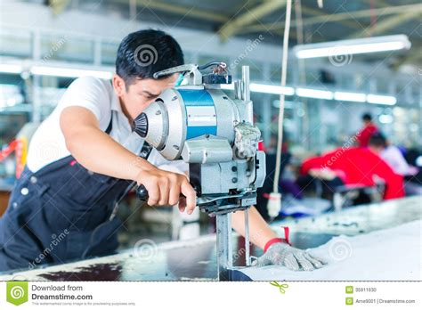 Asian Worker Using A Machine In A Factory Stock Photo